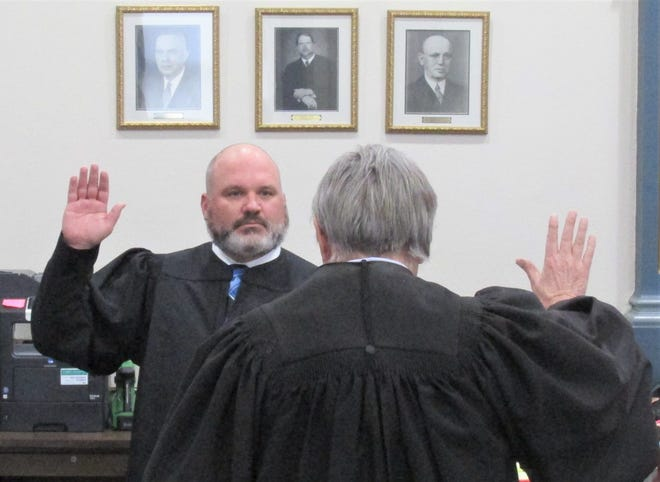 Retiring Holmes County Common Pleas Court Judge Robert Rinfret, with his back to the camera, administers the oath of office to newly elected Common Pleas Court Judge Sean Warner during a brief ceremony Friday afternoon in the Holmes County Common Pleas Court.