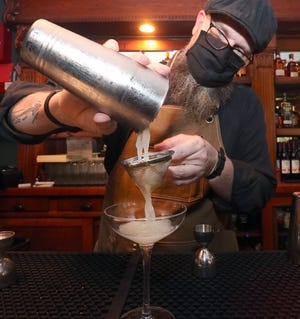 Jay Pouliot pours a B & B's Knees while bartending at Hemingway's 442 inside The DeLand Hotel on Wednesday, Jan. 13, 2021, the opening day for the new upscale speakeasy-themed bar and cigar lounge. The B & B's Knees is comprised of gin, lemon, honey and lavender bitters.