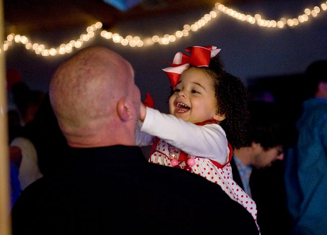 Neveah Christian, 2, laughs with her father, Robert, during Saturday's Fletcher Father-Daughter Dance, held at Calvary Episcopal Church in Fletcher.
