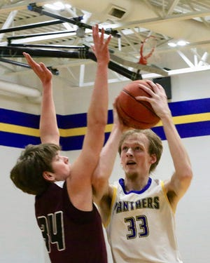 Nickerson's Matt Crossman (33) shoots past Buhler's Jack Voth (34) Thursday evening during a make-up game. Buhler defeated Nickerson 69-38.