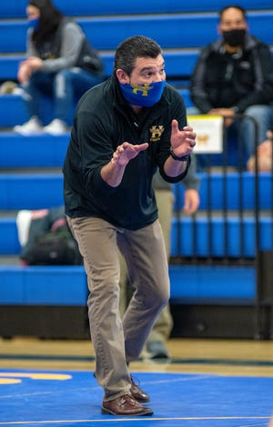 Hutchinson High wrestling coach Jose Garcia gives one of his wrestlers some instruction during their bout Thursday with Maize at the North Gym on the HHS campus. The Salthawks fell 65-6.