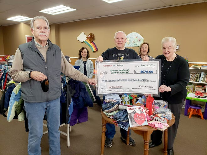 """Bills Frakes, left, Jessica Scheiderman, Ray Matthews, Sally Wagner, and Joanne Schamberger display a symbolic check for money raised from """"Christmas on Chelsea."""" The money was donated Wednesday to Mother Hubbard's Kiddie Cupboard in Freeport."""