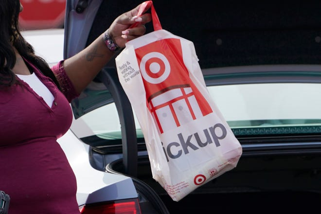 A Target employee places a curbside pickup purchase into the trunk of a customer in Jackson, Miss., shortly before Christmas.
