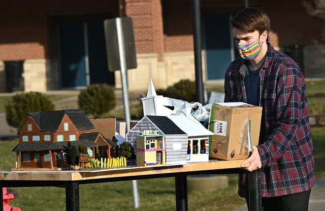 "Natick High School senior Daniel Zogby carries a selection of mini theater sets from the play ""All Really Need to Know I Learned in Kindergarten"", Jan. 15, 2021.  The sets will be placed in Natick storefronts as part of the Redhawk Winter Walk."