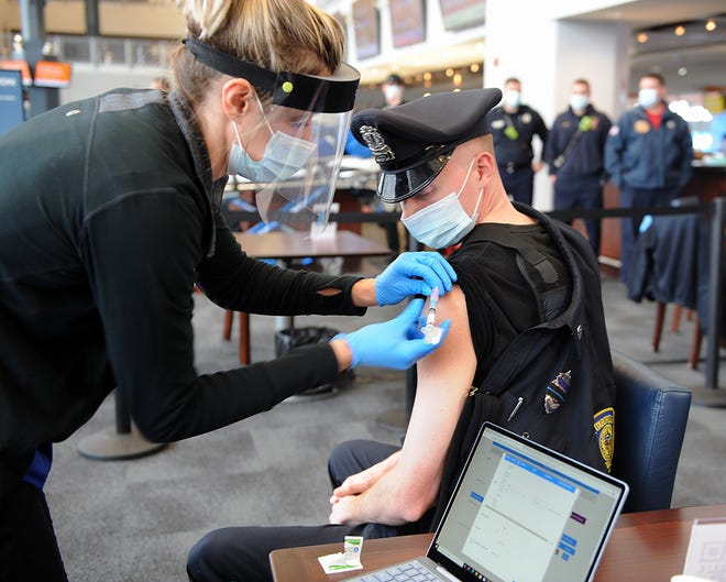 Foxboro Police Officer Brendan Fayles receives a COVID-19 vaccination from RN Samantha Schuko at the Gillette Stadium/CIC Health COVID-19 Vaccination Site on Friday.