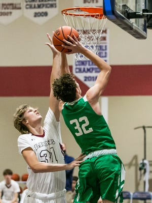Redeemer Christian's Jonah Harrelson blocks a shot by Ocala Christian's Jett Bloom in the first half. The Lions defeated the Crusaders, 51-43, Thursday night.