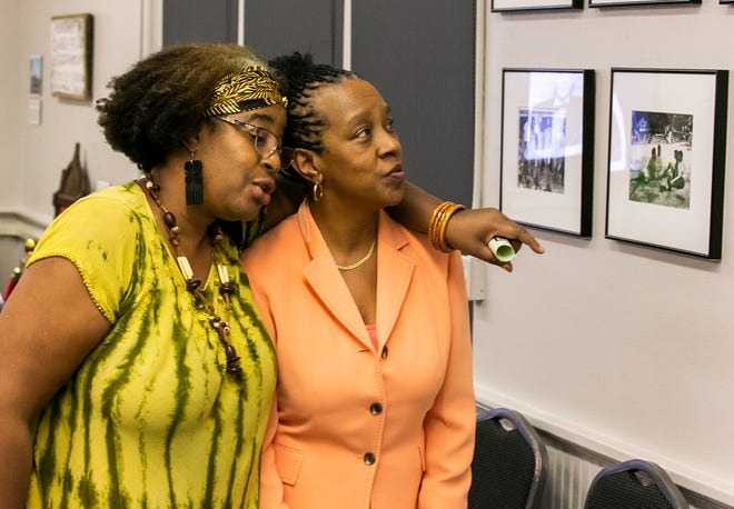 In this file photo from 2019, Cynthia Wilson-Graham, right, pictured with Francine Julius Edwards, left, looks at pictures from Paradise Park, a segregated part of Silver Springs back in the 1950s and 60s.