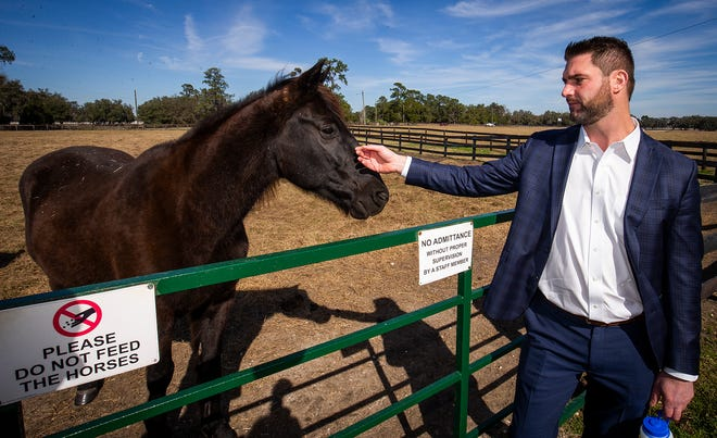Chris Hanaka, director of Transformations at Mending Fences, pets one of the horses, Duke, that are used in therapy at the facility, which sits on 400 acres of horse country in northwest Marion County.