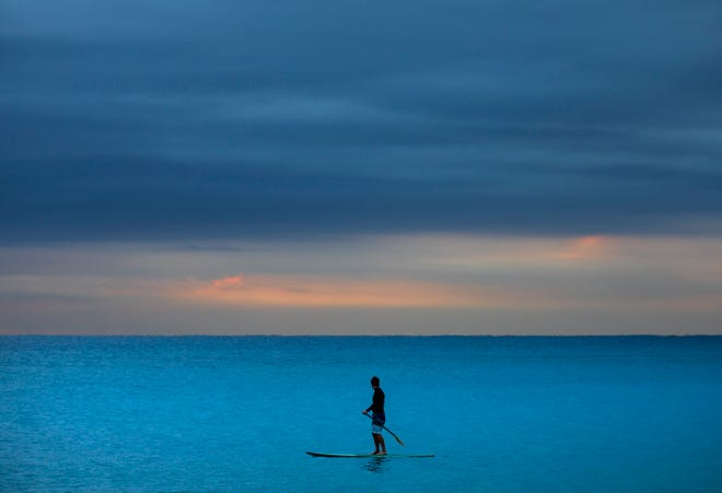 A paddleboarder passes Midtown Beach on the fourth day in a row of a dark dawn in Palm Beach Friday, January 15, 2021.