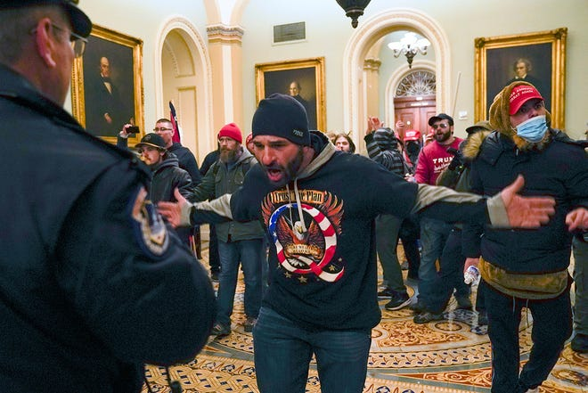 Supporters of President Donald Trump gesture to police in the hallway outside the Senate chamber during the Jan. 6 riot at the Capitol.