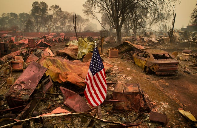 A U.S. flag stands in the middle of the remains of a devastated neighborhood in Talent on Sept. 11, 2020 after the Almeda Fire swept through the area in Southern Oregon.