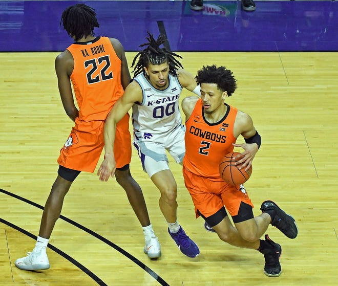 Kansas State guard Mike McGuirl (00) fights through a screen while guarding Oklahoma State's Cade Cunningham (2) during last Saturday's game at Bramlage Coliseum.