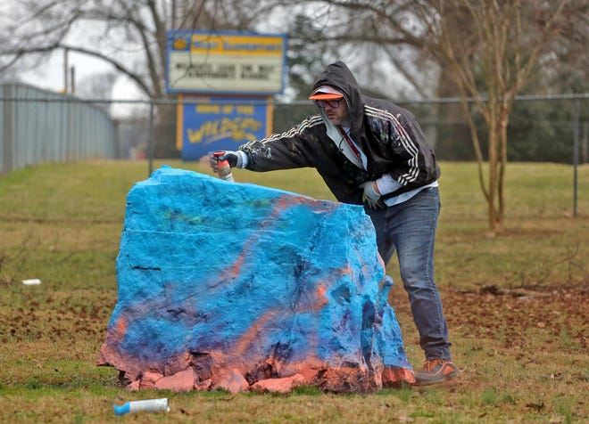 Darrell Endicott adds a base coat of paint to the rock at West Elementary School in Kings Mountain on Friday.