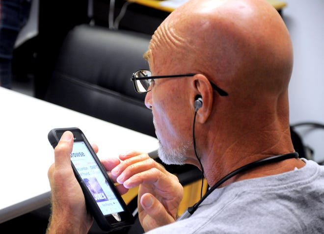 A Lighthouse Vision Loss Education Center client uses an iPhone during a training session.