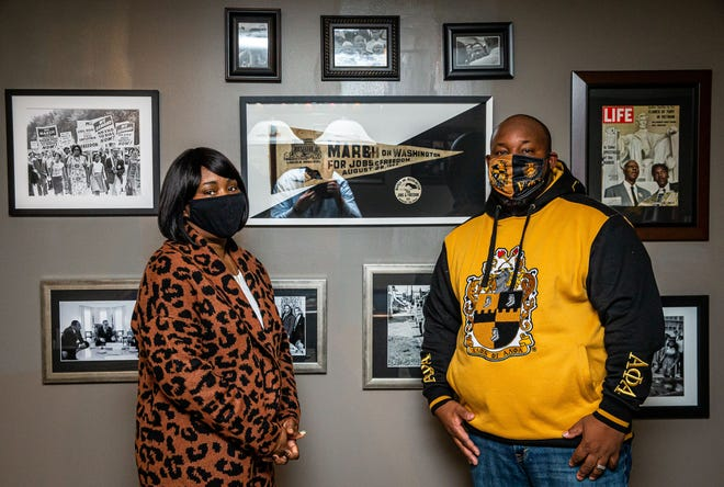 Aaron Pearl-Cropp and his wife, Annie Brooks-Pearl, pose with just a portion of the Martin Luther King Jr. and civil rights movement memorabilia that is displayed in their home including an original pennant and button from the 1963 March on Washington, Thursday, January 14, 2021, in Springfield, Ill. Pearl-Cropp became interested in collecting the memorabilia three years ago after he started an internship at the Central Illinois African American History Museum as a part of his master's degree program. [Justin L. Fowler/The State Journal-Register]