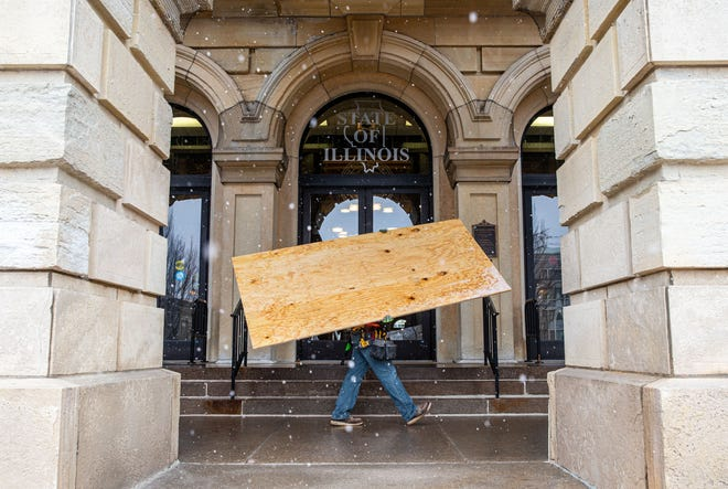 Workers maneuver sheets of plywood into place as they work to cover the first floor windows at the Illinois State Capitol in preparations for possible protests, Friday, January 15, 2021, in Springfield, Ill. Illinois Gov. JB Pritzker announced that he has activated 250 members of the Illinois National Guard amid threats of armed protests in capital cities across the country in the days leading up to President-elect Joe Biden's inauguration. [Justin L. Fowler/The State Journal-Register]
