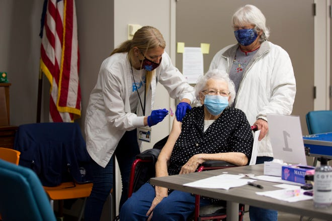A woman receives a COVID-19 vaccine in New Hanover County as part of the Group 1b vaccination phase.