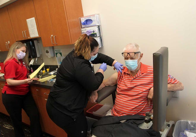Resident Chuck Roeckell receives the COVID-19 vaccine administered by Rachel Mullins, LPN, at a Phase 1b-Group 1 - COVID-19 vaccination event held at CarolinaEast Medical Center facilities at Bern Square in New Bern, NC, Jan. 15, 2021. [Gray Whitley / Sun Journal Staff]