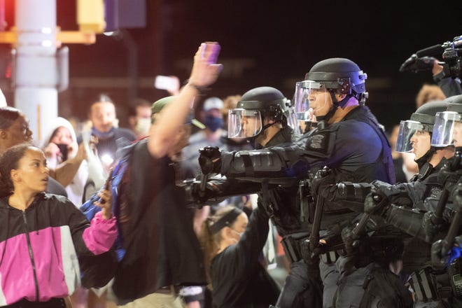 Kansas Highway Patrol officers force back protestors in front of the Law Enforcement Center at 4th Street and Kansas Avenue during protests in the summer.