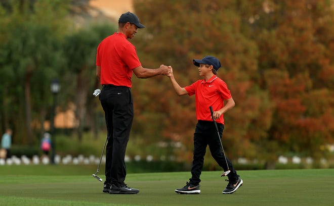 Tiger Woods and son Charlie Woods fist-bump Dec. 20  on the 18th green during the final round of the PNC Championship at the Ritz Carlton Golf Club in Orlando, Florida.