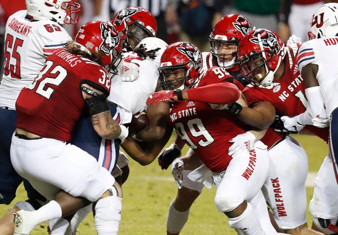 From left, N.C. State's Drake Thomas (32), Alim McNeill (29), Daniel Joseph (99), Isaac Duffy (33) and Isaiah Moore (1) stop Liberty running back Peytton Pickett (25) during the first half of N.C. State's game against Liberty at Carter-Finley Stadium in Raleigh, N.C., Saturday, Nov. 21, 2020.