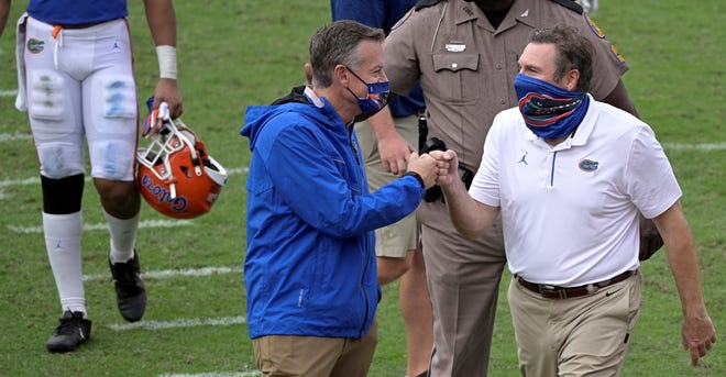 Florida Athletic Director Scott Stricklin, left, says he is confident head football coach Dan Mullen, right, will be the Gators coach for a long time.