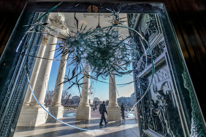 Shattered glass from the Jan. 6 attack on Congress by a pro-Trump mob is seen in the doors leading to the Capitol Rotunda in Washington.