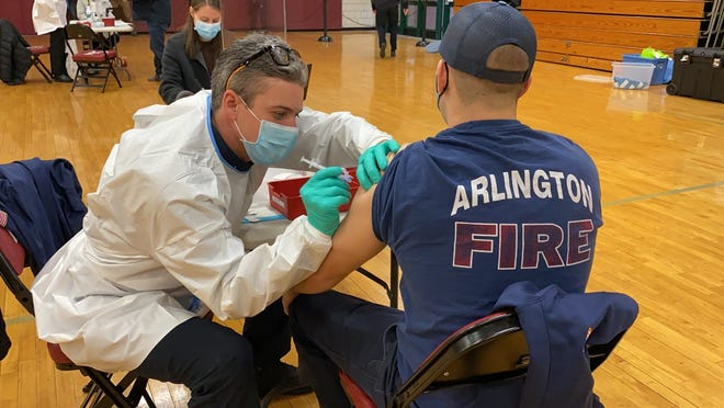 Lt. Liam McDonald administers the vaccine to an Arlington firefighter.