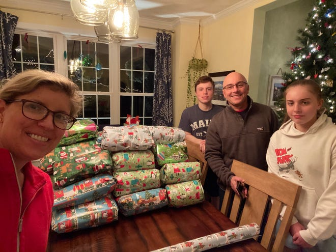Members of St. Stephen Lutheran Church, Marlborough, collected Sweats for Vets and wrapped nearly 300 of them. In the photo, St. Stephen members Christy, Jake, Scott, and Kate Allison wrap the Boston-themed sports team hoodies for homeless veterans all over New England.