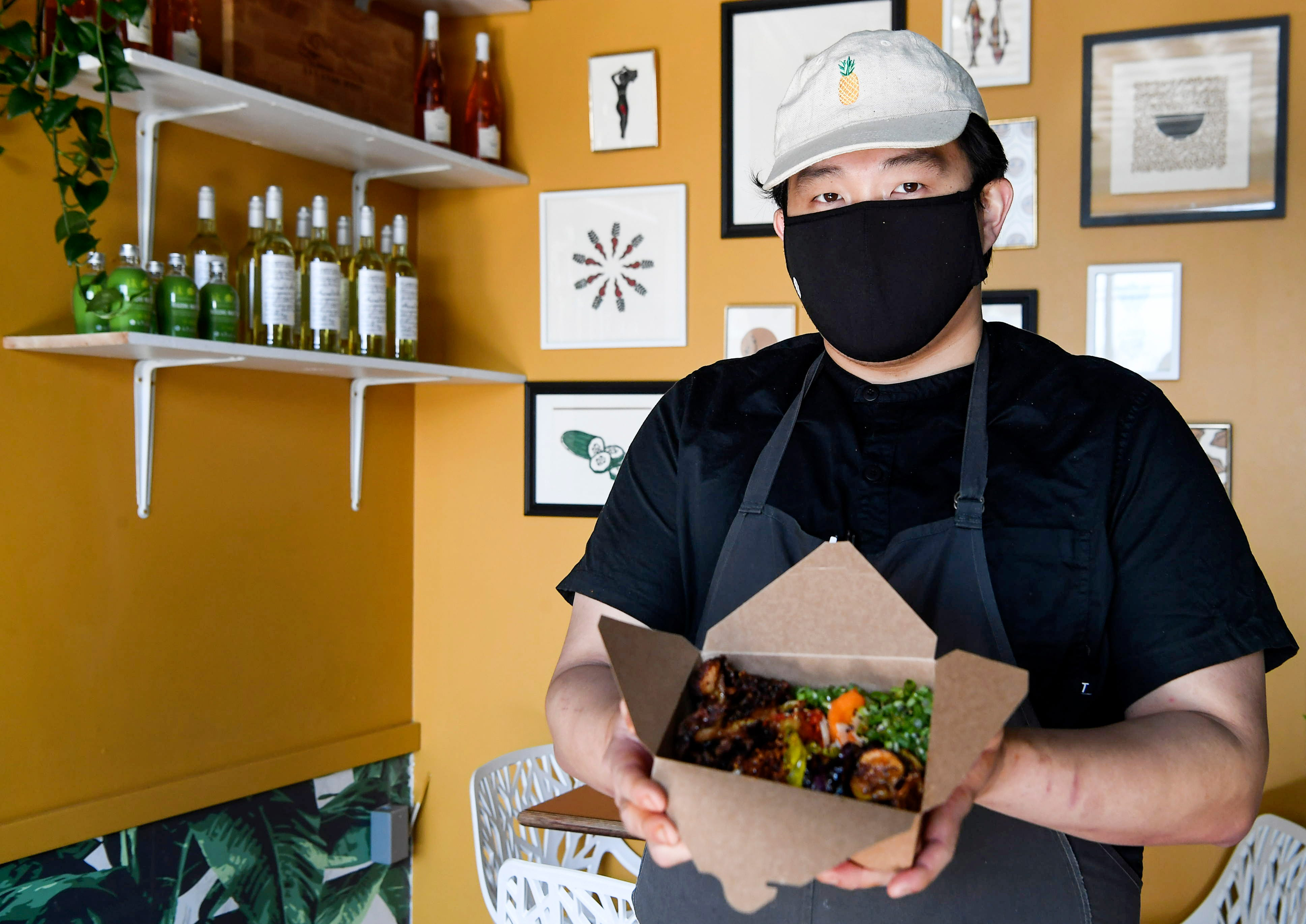 Gan Shan West chef Ray Hui holds the GSW Rice Bowl with black bean chicken, which comes with eggplant rubbed in togarashi, house pickles and kimchi, sweet soy, Japanese mayo, chili oil and peanuts.