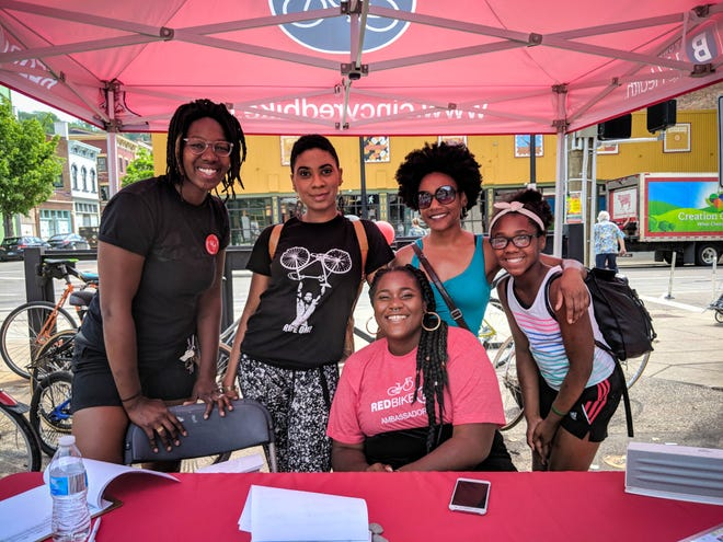 """Besides her work in the arts, phrie (second from left) organized """"100 Blacks on Bikes."""" She's seen here with a group of riders and volunteers."""
