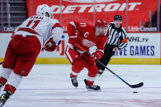 Detroit Red Wings center Dylan Larkin (71) collides with Carolina Hurricanes center Jordan Staal (11) during the third part of the season opener at Little Caesars Arena in Detroit on Thursday January 14. 2564