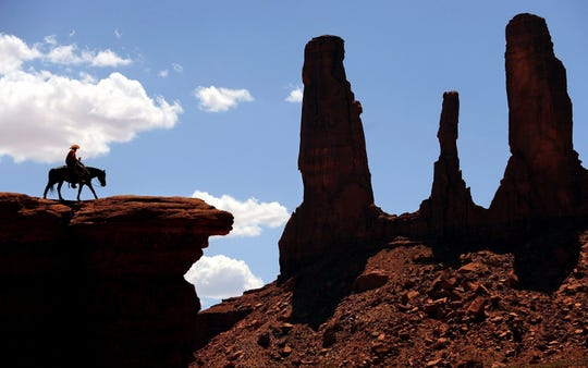 A man on a horse walks on John Fords Point beneath the Three Sisters in Monument Valley on the Utah/Arizona border in a July 2014 file image.