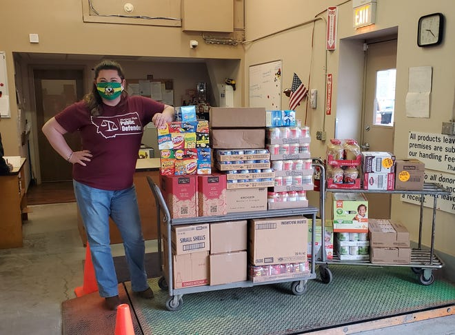 Public defender Claire Lettow shows off the 700 pounds of food purchased by her office for the Great Falls Community Food Bank.