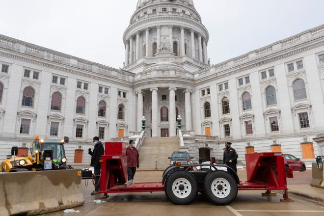 Under the supervision of a Capitol Police sergeant, a barricade is placed on the E. Washington Ave.side of the Capitol Friday, January 15, 2021 in Madison.
