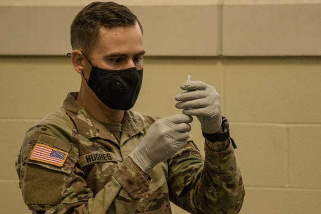 Alabama National Guard Medical Detachment Soldier preparing a does of COVID-19 vaccine on Jan. 7, 2021.