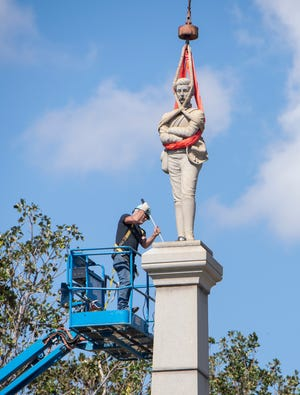 A worker pries the statue from its base as they begin to disassemble the Confederate monument in downtown Pensacola on Oct. 26, 2020. The Pensacola City Council voted 6-1 to remove the monument on July 14.