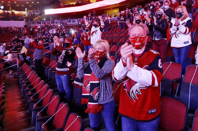 Jan 14, 2021; Glendale, AZ, USA; Jerry and Rebecca Gehrke clap wearing their Coyotes masks as the team takes to the ice before the first period against the Sharks at Gila River Arena. Mandatory Credit: Patrick Breen-Arizona Republic
