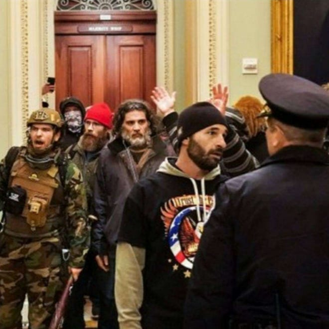 Federal prosecutors say the bearded man in the center of the photograph is Dominic Pezzola of Rochester.
