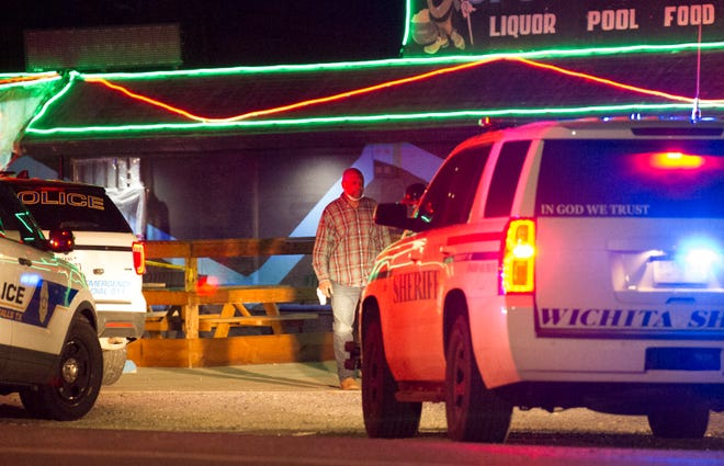 James Henderson Jr. waits to be interviewed by police at the scene of O'Brien's Sports Pub.