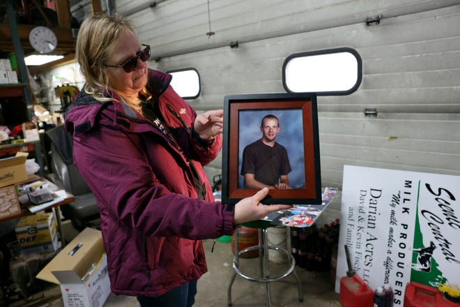 Amy Fischer is seen with a photo of her son, Brian, on her family's 350-cow dairy farm, Darian Acres, in Rio, Wis., on Dec. 18, 2020. Brian died by suicide at the age of 33, on Dec. 21, 2016. The Fischers attribute his death to a combination of stress from work, a drinking problem and depression from a recent break-up. Dairy farmers and their advocates say numerous stressors are leading to a mental health crisis in their industry, including financial pressures, long hours, labor shortages and harsh weather.