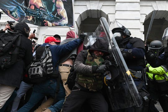 On Jan. 6, riot police push back a crowd of President Donald Trump's supporters after they stormed the Capitol building in Washington, DC.
