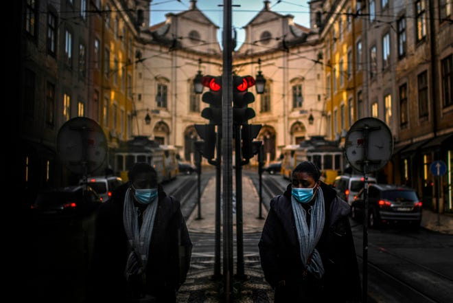 A woman wearing a face mask is reflected in a shop window while walking in Lisbon on Jan. 15, 2021 as Portugal entered a fresh lockdown over a surge in coronavirus cases.