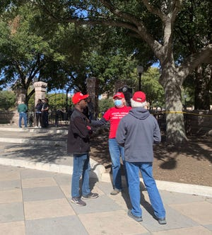 "A small group of people wearing ""Trump 2020"" and ""Make America Great Again"" hats gathered at the Texas Capitol on Saturday afternoon."