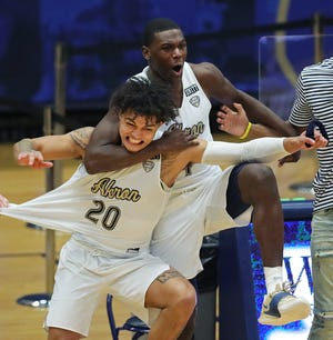 University of Akron junior Michael Wynn, left, celebrates with Jermaine Marshall after the Zips beat the Toledo Rockets 95-94 in overtime, Saturday, Jan. 16, 2021, in Akron, Ohio. [Jeff Lange/Beacon Journal]