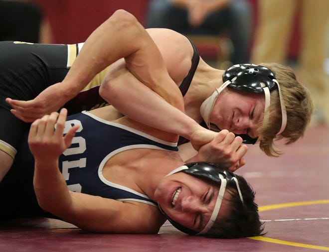 Stow-Munroe Falls' JT Hill, top, works over Solon's Ricky Berns during their 152-pound match in a tri-meet at Walsh Jesuit High School, Saturday. [Jeff Lange/Akron Beacon Journal]