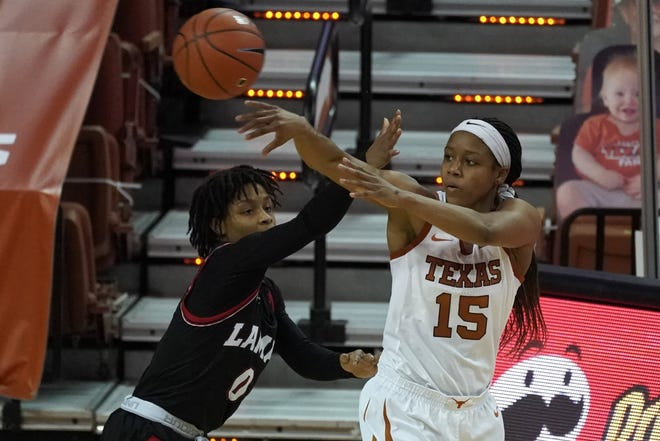 Texas point guard Kyra Lambert (15) passes the ball over Lamar's Kayla Mitchell (0) in Austin on Dec. 30, 2020.