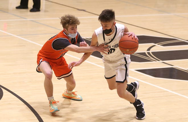 South Side's Aidan Roach (right) drives to the basket while being guarded by Springdale's Chris Hitchell (left) during the first half Friday night at South Side Area High School.