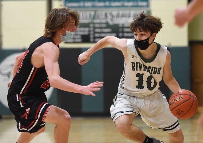 Riverside guard Garrett Dwyer (10) dribbles around Mohawk's Keigan Hopper during Friday night's game at Riverside High School.