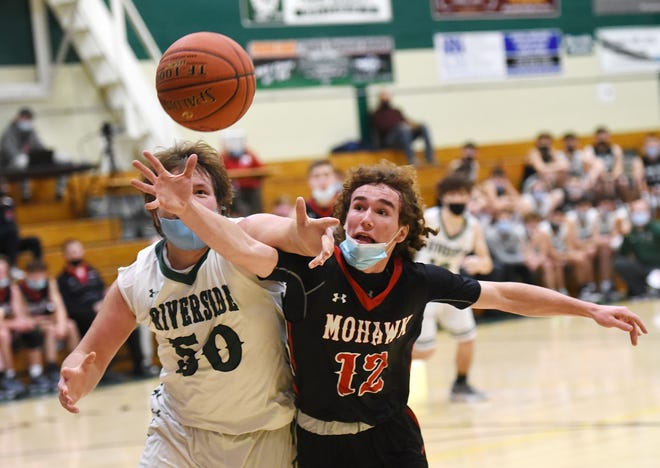 Riverside's Avery Wolf and Mohawk's Jay Wrona battle for a rebound during a game earlier this season. Four area boys' teams, including Riverside, and four area girls' teams have opted out of the WPIAL basketball playoffs.